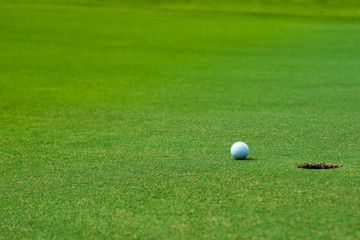 Golf ball on green near golf hole Concept of success, win