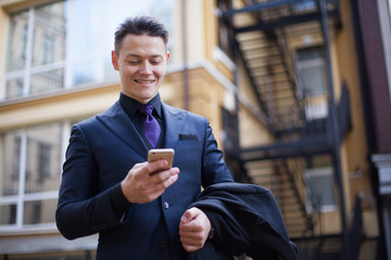 Smiling stylish man in a coat with a smartphone smiling.
