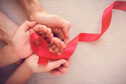 adult and child hands holding red ribbon, hiv awareness concept, world AIDS day, world cancer day
