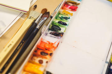 Classic natural brushes for drawing with watercolors and a palette with different paints prepared for drawing.