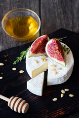 Camembert cheese with fresh figs, honey and pine nuts on dark wooden cutting board. Closeup view