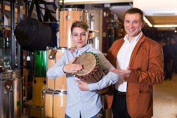 Teenage and father choosing ethnic drum