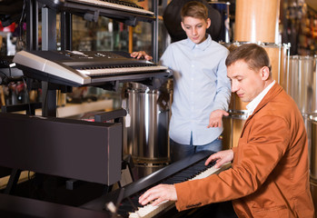 Father and teenage son examining keyboards in guitar shop