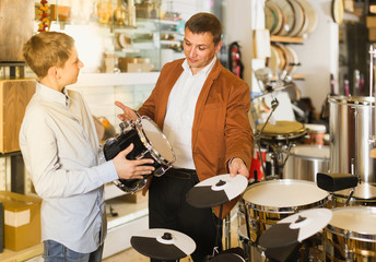 Father and teenage son examining drum units in guitar shop