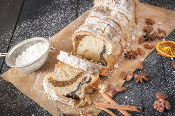 Sliced sponge cake and powdered sugar - Delicious homemade pound cake on a baking paper, surrounded by roasted walnuts and almonds, covered in powdered sugar, on a black wooden table.
