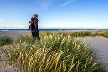 Young woman hiking in coastal dune grass at beach of North Sea.