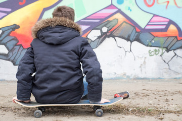A young boy sitting on a skateboard looking at his work