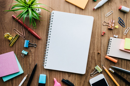 Top view of blank notepad and office supplies on wood background.business creativity and inspiration concepts