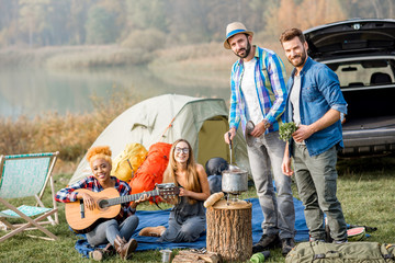 Multi ethnic group of friends dressed casually having a picnic, cooking soup with cauldron, playing guitar during the outdoor recreation near the lake