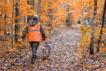Hunting dog with hunters in forest.