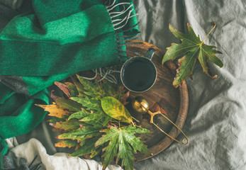 Fall morning tea in bed. Flat-lay of mug of tea with sieve and colorful fallen leaves on rustic wooden tray over bed linen and blanket background, top view. Autumn mood concept