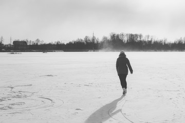 skating. black and white photograph. a girl riding on the lake on skates
