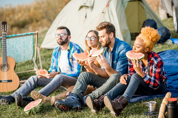 Multi ethnic group of friends having a picnic, eating watermelon during the outdoor recreation with tent, car and hiking equipment near the lake