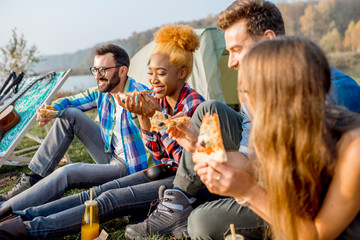 Multi ethnic group of firends dressed casually having fun eating pizza during the outdoor recreation at the camping