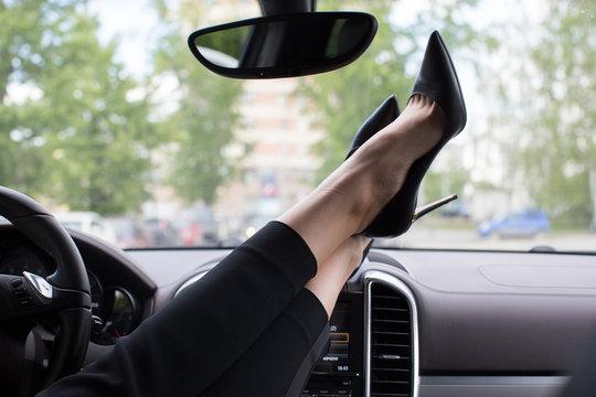 Woman feet heels on car dashboard car interior