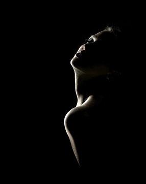 Sensual portrait of woman in shadow on dark background
