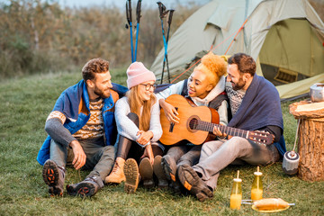 Multi ethnic group of friends dressed in sweaters playing music together and warming up with plaid at the camping during the evening time