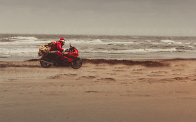Winter beach  with Santa on a heavy red motorcycle