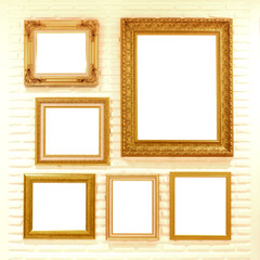 empty golden picture frames on brick wall