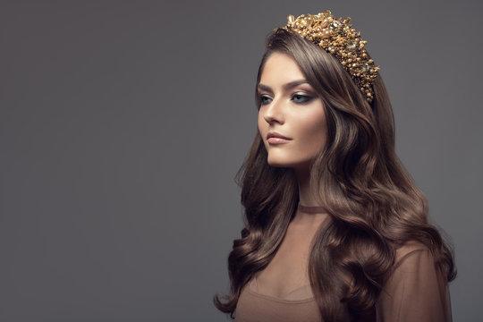 Beautiful woman in gold crown on her head. Long wavy brown hair.