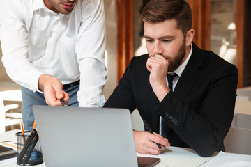 Close-up photo of two young man sitting in office and discussing business using laptop