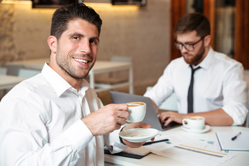 Portrait of a smiling handsome businessman drinking coffee