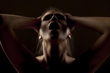 portrait of screaming woman in shadow on dark background