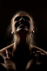 portrait of screaming woman in shadow on dark background
