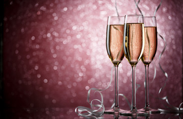 Picture of three wine glasses with champagne on pink background
