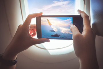 Female taking a photo with smartphone on plane.Holiday travel and journey concepts