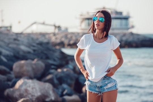 Girl in a white t-shirt on the background of the ocean. Mock-up.