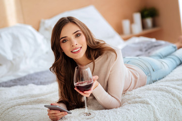 Relaxed girl enjoying glass of wine while resting at home