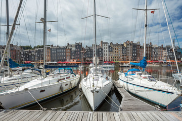 Yachts moored at quay port of Honfleur, France. Concepts of success, leisure, holiday, rich, tourism, luxury, lifestyle. Sunny Summer, blue sky