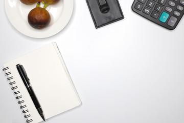 a notebook, a calculator and a pen on a desk