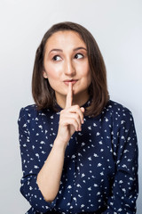 Woman saying hush be quiet with finger on lips gesture isolated on gray wall background. Portrait of emotional girl, saying 'shh', asking for silent or to keep her secret. Human face expressions.