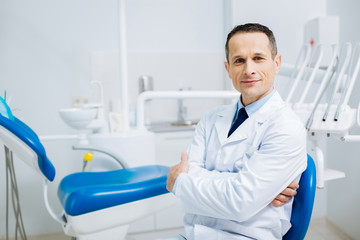 Handsome delighted doctor looking at you