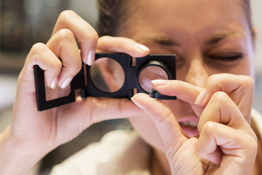 Jeweler looking at stone through loupe to inspect it. Close up shot. Focus on the jewellery.