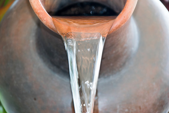 Close up Pour water out of terracotta pots.