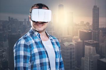 Smiling positive man wearing virtual reality glasses