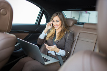 Beautiful business woman working on laptop in a limousine
