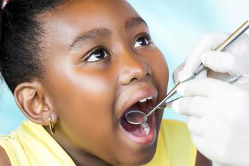 Little black girl having dental checkup.