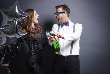 Couple uncorking bottle of champagne