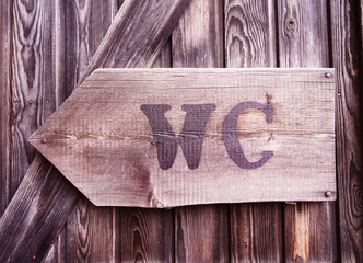 An old, wooden restroom sign with arrow