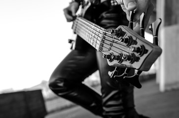 Close-up photo of electric bass guitar player.  Live music background, electric bass guitar