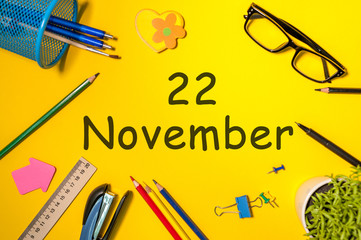 November 22nd. Day 22 of last autumn month, calendar on yellow background with office supplies. Business theme