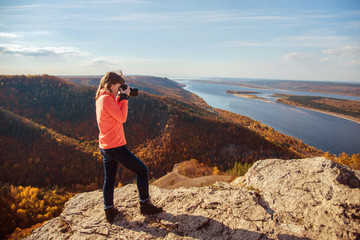 the girl stands on top of the mountain and takes pictures of the landscape