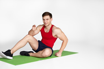 Muscular man sitting on mat