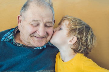 portrait of a Happy Boy Kissing Happy granddad