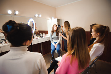 professional makeup teacher training her student girl to become makeup artist. Makeup tutorial lesson at beauty school. Master class. Real people.