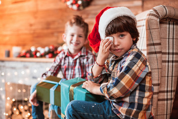 Beautiful happy laughing children brothers  play with gifts in hand in a Christmas interior with a Christmas tree. The concept of a family holiday